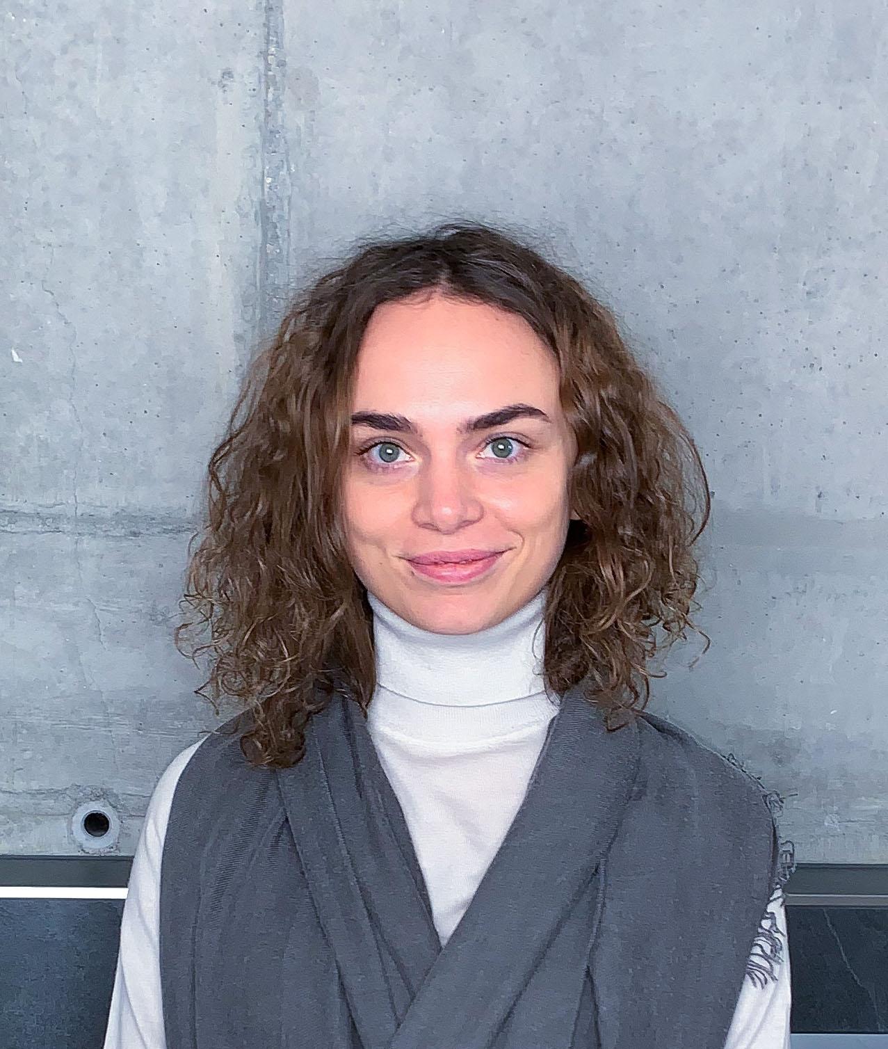 Bild eines jungen Dame mit weißem Rollkragenpullover mit welligen Haaren